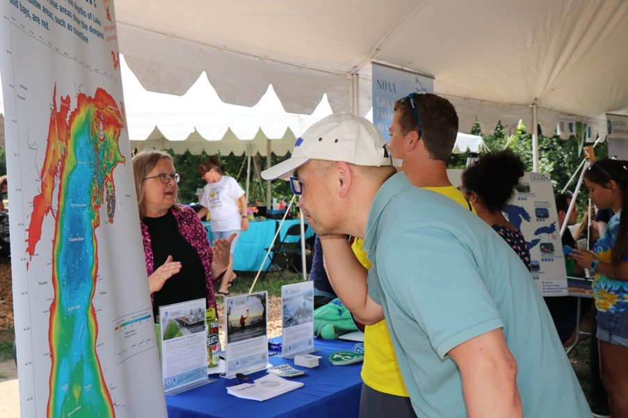 Outreach Specialist Michele Wensman enjoys talking about CIGLR's Great Lakes research while guests check out the 3D maps illustrating the depth of the Great Lakes. Photo Credit: GLERL.